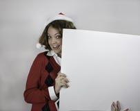 Ładna młoda kobieta jest ubranym Santa mienia pustego miejsca kapeluszowego znaka Obraz Royalty Free