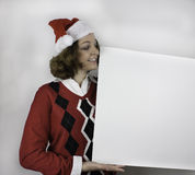 Ładna młoda kobieta jest ubranym Santa mienia pustego miejsca kapeluszowego znaka Zdjęcia Stock