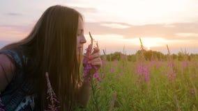Ładna młoda kobieta obwąchuje kwiatu pole przy zmierzchem Piękna kobieta wdycha woń kwiaty zbiory wideo
