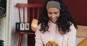 Ładna młoda kobieta ono uśmiecha się podczas gdy gawędzący na żółtym smartphone obsiadaniu na łóżku w domu Dziewczyna wysyła wiad zbiory wideo