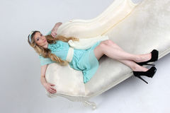 Ładna młoda kobieta opierająca z powrotem na białej kanapie Zdjęcie Stock