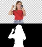 Ładna młoda kobieta patrzeje w prostuje jej włosy mobilnym, Alfa kanale, zdjęcie stock