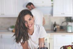 Ładna młoda kobieta pije niektóre wino w kuchni w domu fotografia royalty free