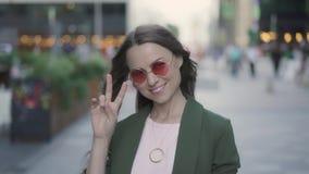 Ładna młoda kobieta pokazuje zwycięstwo podpisuje wewnątrz spadek ulicę zbiory