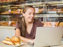 Ładna młoda kobieta pracuje przy komputerem i je chleb Unheal Obrazy Stock