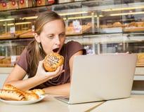 Ładna młoda kobieta pracuje przy komputerem i je chleb Unheal Obraz Royalty Free