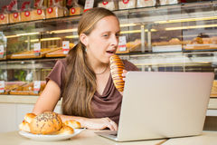 Ładna młoda kobieta pracuje przy komputerem i je chleb Unheal Obraz Stock