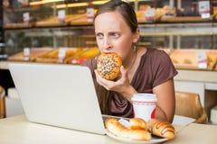 Ładna młoda kobieta pracuje przy komputerem i je chleb Unheal Zdjęcie Stock