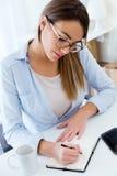 Ładna młoda kobieta pracuje w jej biurze Zdjęcia Royalty Free