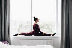 Ładna młoda kobieta robi joga ćwiczeniu na okno w domu zdjęcie stock