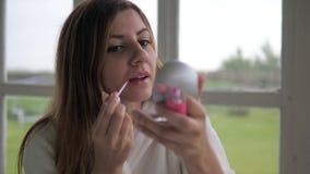 Ładna młoda kobieta rozmazów wargi glosa i spojrzenia w lustrze zbiory wideo