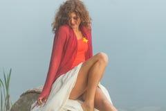 Ładna młoda kobieta siedzi na kamieniu zdjęcia royalty free