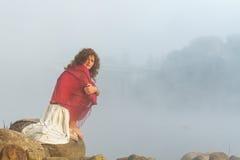 Ładna młoda kobieta siedzi na kamieniu obrazy stock