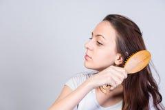 Ładna młoda kobieta szczotkuje out ona długie włosy Obrazy Royalty Free