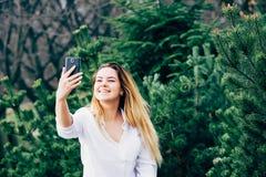 Ładna młoda kobieta uśmiecha się selfie w parku i robi obraz royalty free