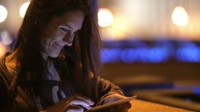 Ładna młoda kobieta używa jej pastylkę przy nocą Ono uśmiecha się, wiatr dmucha jej włosianego, zamazanego tło, wolny mo zbiory wideo