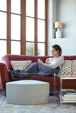 Ładna młoda kobieta używa jej telefon komórkowego podczas gdy pijący kawę na kanapie w domu zdjęcia stock