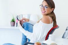 Ładna młoda kobieta używa jej telefon komórkowego w biurze Zdjęcia Royalty Free