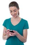 Ładna młoda kobieta używa smartphone zdjęcie stock