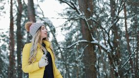 Ładna młoda kobieta w żółtej kurtce biega wokoło zima lasu zbiory