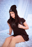 Ładna młoda kobieta w Czarnym obsiadaniu na łóżku fotografia royalty free