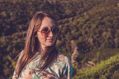 Ładna młoda kobieta w górach na zmierzchu czasie Zdjęcia Stock