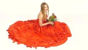 Ładna młoda kobieta w pięknej czerwieni sukni, siedzi zdjęcie wideo
