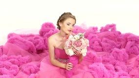 Ładna młoda kobieta w wspaniałej menchii sukni, siedzi zdjęcie wideo