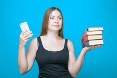 Ładna młoda kobieta z książkami w telefonie komórkowym i rękach obraz stock