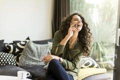 Ładna młoda kobieta z telefonem komórkowym w pokoju fotografia stock