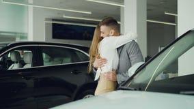 Ładna młoda kobieta zamyka jej męża ` s oczy i prowadzący on nowy samochód w samochód sala wystawowej, excited mężczyzna jest zdjęcie wideo