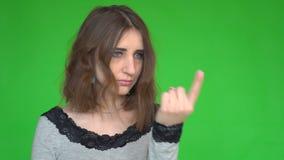 Ładna młoda kobieta zaprasza przychodzić podczas gdy patrzejący kamerę nad zielonym tłem zdjęcie wideo