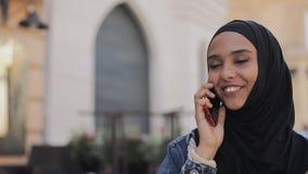 Ładna młoda Muzułmańska kobieta jest ubranym hijab kierowniczego szalika iść na stary centrum miasta i opowiada na telefonie zbiory wideo
