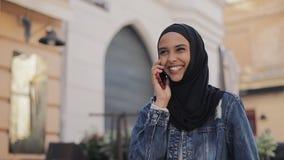 Ładna młoda Muzułmańska kobieta jest ubranym hijab kierowniczego szalika iść na stary centrum miasta i opowiada na telefonie zdjęcie wideo