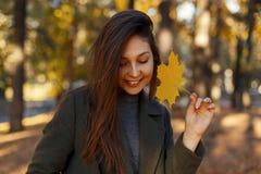 Ładna młoda szczęśliwa kobieta z uśmiechem z żółtym jesień liściem chodzi w parku na słonecznym dniu fotografia royalty free