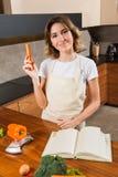 Ładna młodej damy łasowania marchewka w kuchni Zdjęcie Stock