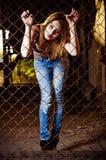 Ładna młodej dziewczyny pozycja za kruszcowym ogrodzeniem obraz stock