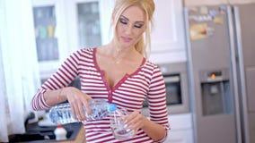 Ładna młodej kobiety dolewania woda butelkowa zbiory
