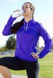 Ładna młodej kobiety woda pitna po biegać Zdjęcie Stock
