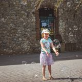 Ładna mała dziewczynka bawić się z dużymi bąblami w ulicie w letnim dniu zdjęcia royalty free