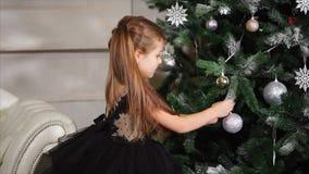 Ładna mała dziewczynka dekoruje choinki, stawia na srebnej piłce zdjęcie wideo