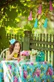 Ładna mała dziewczynka je truskawki i spojrzenia przy kamerą przy stołem Fotografia Stock