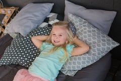 Ładna mała dziewczynka kłama na łóżku i ono uśmiecha się Obraz Stock