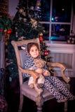 Ładna mała dziewczynka ono uśmiecha się z misiem blisko choinki obsiadania w rocznika krześle szczęśliwego nowego roku, Zdjęcia Royalty Free