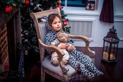 Ładna mała dziewczynka ono uśmiecha się z misiem blisko choinki obsiadania w rocznika krześle szczęśliwego nowego roku, Obraz Royalty Free
