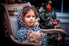 Ładna mała dziewczynka ono uśmiecha się z misiem blisko choinki obsiadania w rocznika krześle szczęśliwego nowego roku, Fotografia Stock