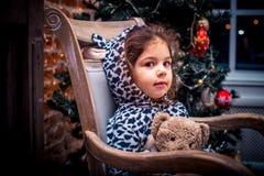 Ładna mała dziewczynka ono uśmiecha się z misiem blisko choinki obsiadania w rocznika krześle szczęśliwego nowego roku, Obrazy Stock