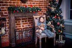 Ładna mała dziewczynka ono uśmiecha się z misiem blisko choinki obsiadania w rocznika krześle szczęśliwego nowego roku, Fotografia Royalty Free