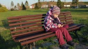 Ładna mała dziewczynka używa app na smartphone siedzi na ławce w parku zbiory
