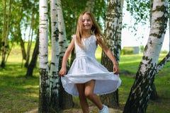 Ładna mała dziewczynka w biel sukni kłębi i tanczy wśród drzew obrazy royalty free